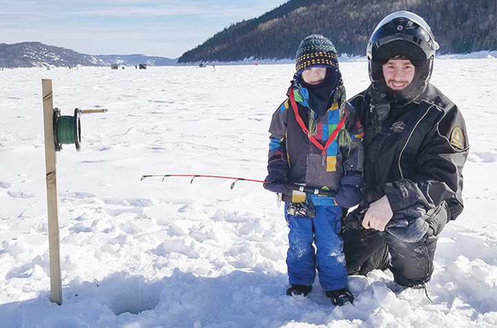 A Fishery Officer with a child fishing in the Saguenay Fjord